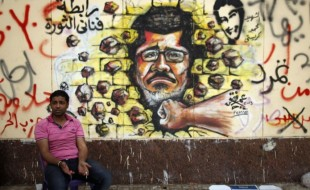 Protester_opposing_President_Mohamed_Morsi_sits_next_to_graffiti_depicting_Morsi_on_a_wall_in_Cairo_1-Jul-2013VOA