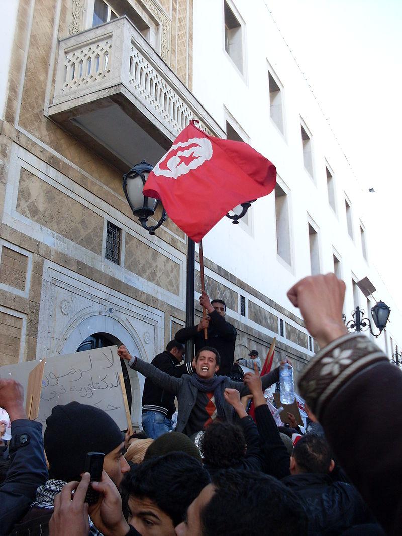 23 gennaio 2011: contestatori antigovernativi sventolano la bandiera della Tunisia - M. Rais